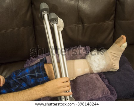 Man With a Sprained Ankle on Couch Holding Crutches