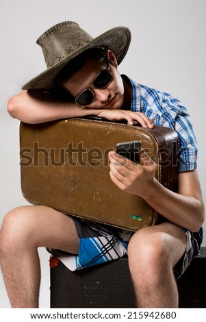 Man with a suitcase is waiting phone call. A young man wearing a hat and sunglasses - stock photo