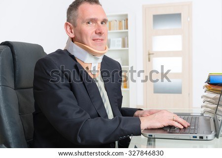 Man with a surgical cervical collar suffering from neck pain at work - stock photo