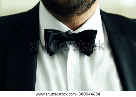 Man with a thick black beard in luxurious white shirt and black jacket with tie butterfly closeup. Wedding background.