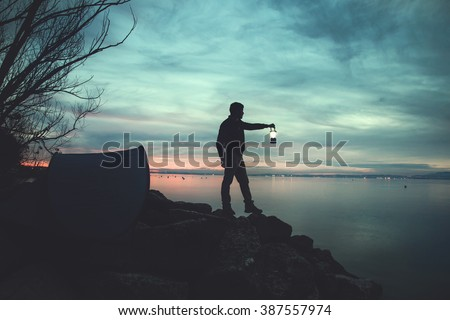 Man with a torch camping in the lake at night - stock photo