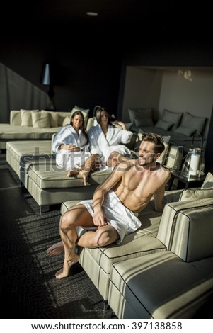 Man with a towel sitting in a room - stock photo