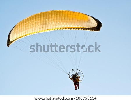 Man with a yellow paraglider flying in the sky - Perth Australia - stock photo