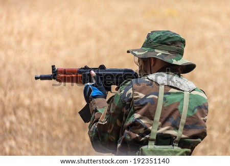 man with an AK holding at gunpoint, the military conflict