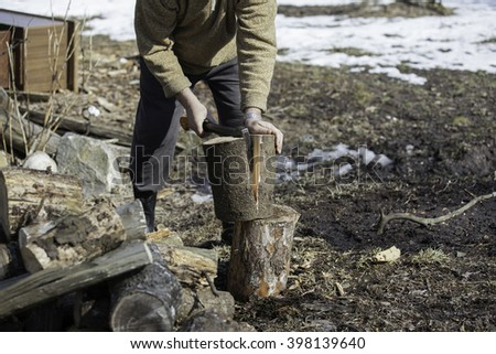 Man with an ax chops firewood