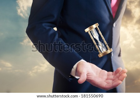 man with an hourglass floating on his hand, time concept - stock photo