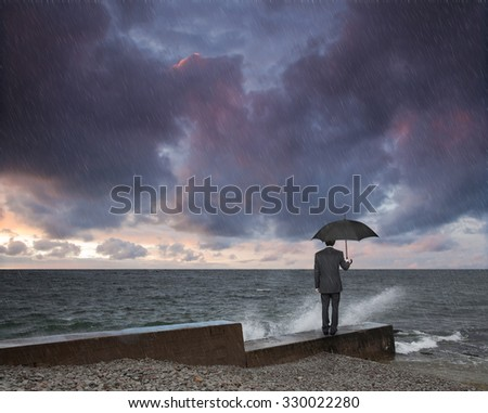 man with an umbrella in a storm - stock photo