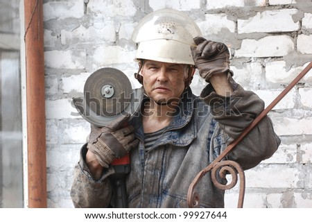 Man  with angular electric grinder. Ukraine - stock photo
