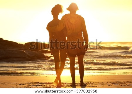 Man with arm around woman standing at the beach watching sunset together  - stock photo