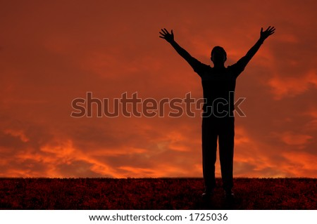 Man with arms extended toward heaven at sunset