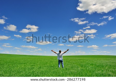 man with arms raised on a green field under beautiful sky - stock photo
