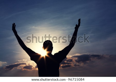 man with arms wide open is looking at the sky - stock photo
