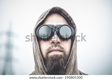 man with aviator glasses in a desolate landscape  - stock photo