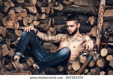 Man with ax in hands near firewood stock
