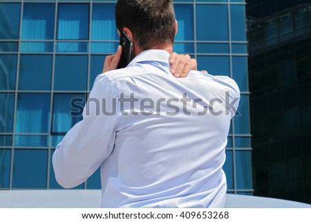 Man with  back pain. Business man rubbing his painful neck  - stock photo