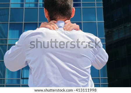 Man with  back pain. Business man rubbing his painful neck
