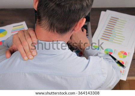 Man with back pain. Business man rubbing his painful neck close up - stock photo