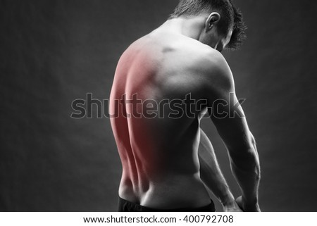 Man with backache. Pain in the human body. Handsome bodybuilder posing on gray background. Black and white photo with red dot - stock photo