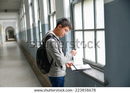 Man with backpack and schoolbooks at college