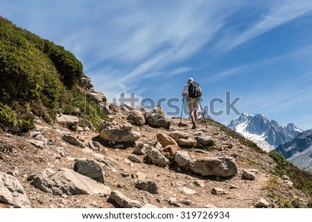 Man with backpack climbs the footpath to the mountains