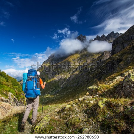 Man with backpack hiking in Caucasus mountains in Georgia - stock photo