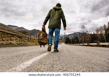 man with backpack in hand walking alone down a mountain road - stock photo