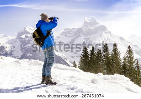 Man with backpack is standing on a mountain and looking through binoculars. - stock photo
