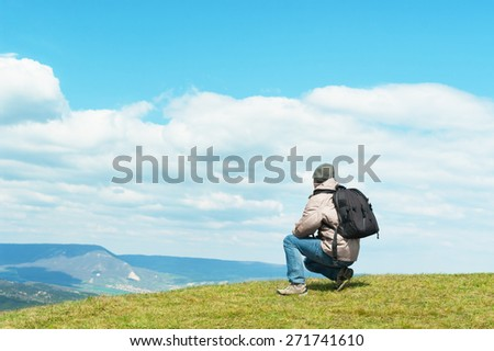 Man with backpack looking away on top of the hill. - stock photo