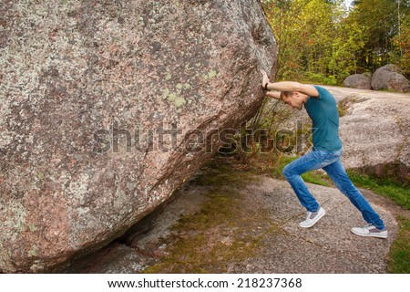 Man with backpack pushing a huge stone - stock photo
