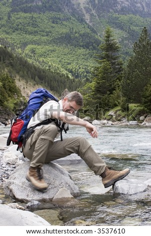 Man with backpack resting on a stone in a mountain river - stock photo
