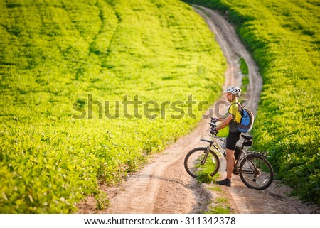 Man with Backpack Riding a Bicycle on Beautiful Nature Background - stock photo