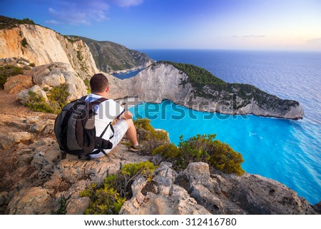 Man with backpack sitting watching sunset over Navagio beach on Zakynthos island, Greece - stock photo