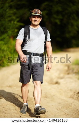Man with backpack trekking in a rural area with forest and dirt road, full length