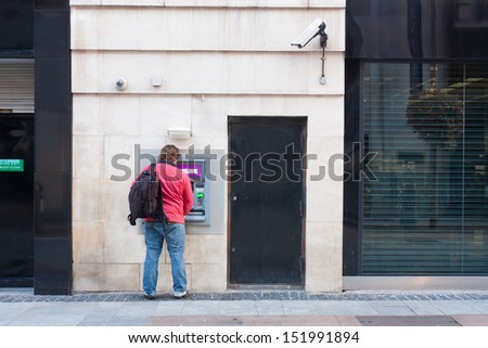 Man with backpack using an ATM - stock photo