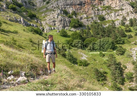 Man with backpack walking at the mountains in the summer