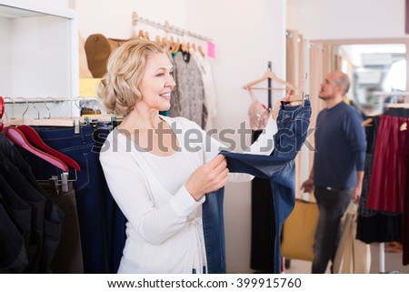 Man with bags waiting for woman choosing jeans in boutique - stock photo