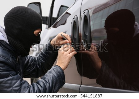 Man with balaclava on head trying to break into car