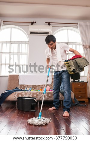 Man with basket of dirty clothes mopping floor in his room - stock photo
