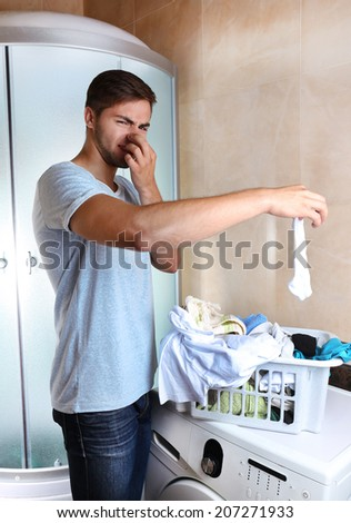 Man with basket of laundry, indoors