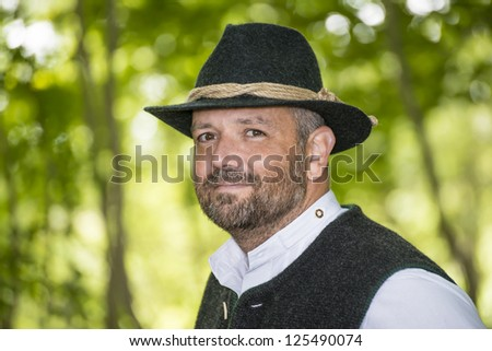 Man with Bavarian traditional black hat in forest