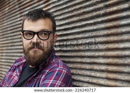 Man With Beard And Glasses Posing On Rainy Day Next To Garage Background