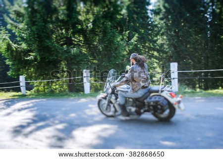 Man with beard driving his cruiser motorcycle by nice road in the forest. Man is wearing leather jacket and blue jeans. Back view. Tilt shift lens blur effect - stock photo