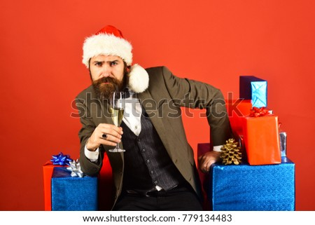 Man with beard holds champagne. New year eve concept. Santa in retro suit near blue and red gifts. Businessman with confident face by stack of boxes and glass of drink on red background