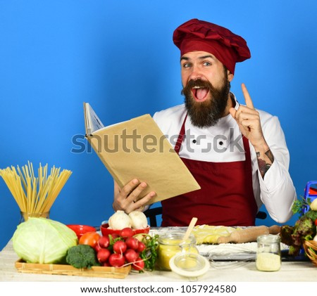 Man beard holds recipe book menu stock photo royalty free man with beard holds recipe book or menu on blue background chef has new idea forumfinder Image collections