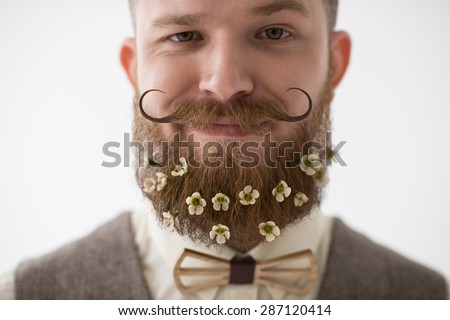 Man with beard in flowers closeup portrait on white background with natural light - stock photo