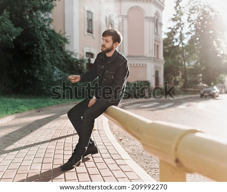 Man with beard in jute and jeans sitting beside the road with a cigarette and smokes - stock photo