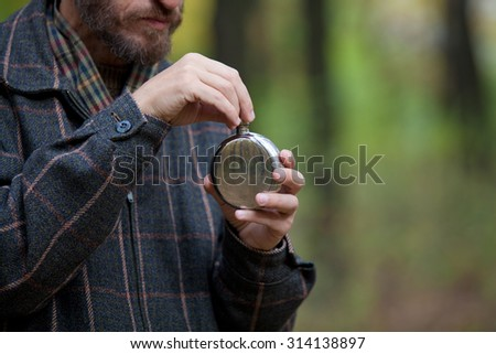 Man with beard in plaid jacket opens metal flask round shape