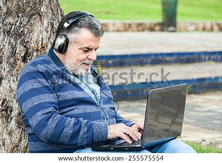 Man with beard listening to music in a park
