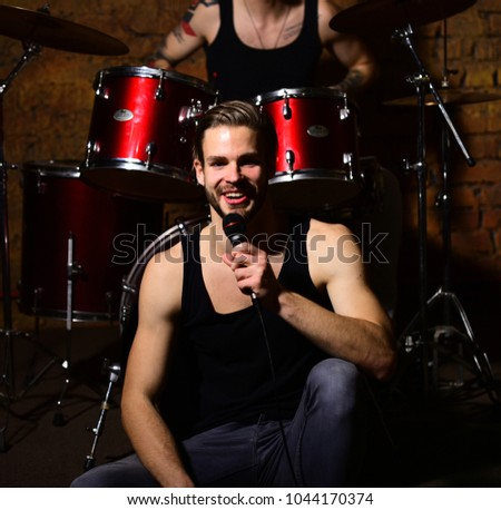 Man with beard sings on bar instruments background. Singer or star with smiling face sings sitting on scene. Rock group and music concept. Guy with microphone sings in studio or bar.