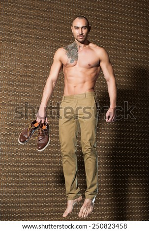 man with beautiful muscular body posing with shoes in hands. Tattoo - stock photo